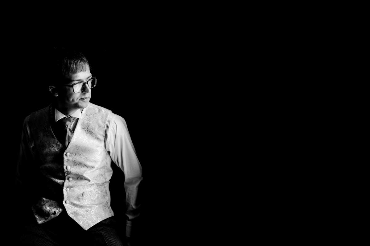 Groom along before his wedding, in dramatic lighting