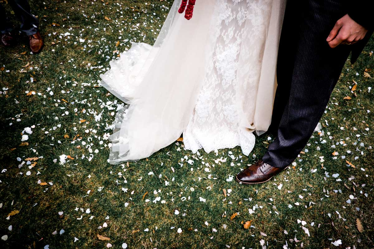 Confetti on floor by groom and bride