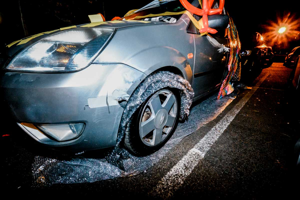 Guests putting post-it notes all over the bride and groom's wedding car